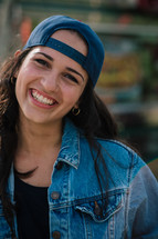 A smiling young woman with her cap on backwards.
