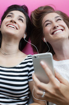 Two young women laughing and listening with ear phones.