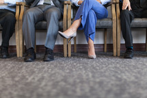 legs of men and women in a waiting room