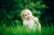 girl child playing in green grass