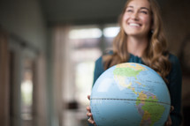 A smiling young woman holding a globe.