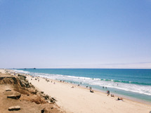 People sunbathing on a long sandy beach at the ocean.