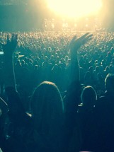 a woman standing with hands raised in the air at a concert