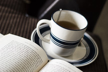 Cup of coffee and an open book.