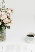 open Bible, coffee cup, and vase of flowers