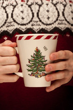 a man in a sweater holding a Christmas mug