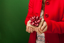 a woman in a red peacoat holding a gift box