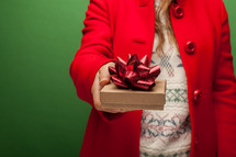 a woman in a red coat holding a Christmas gift