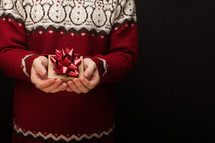 a man in Christmas sweater holding a gift box