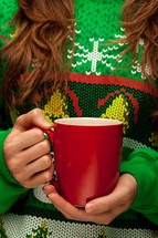a woman in a Chrisms sweater t-shirt holding a mug