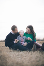 mother father and toddler son sitting in a field