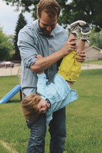 a father holding his son upside down by his feet
