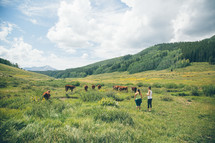 women near cows grazing in a pasture