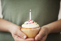 hands holding a birthday cupcake