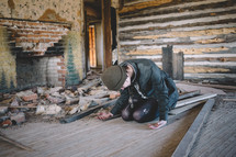 A woman sits on the floor in prayer in an abandoned house.