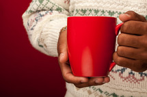 holding a red mug wearing a sweater
