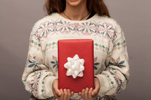 a woman in a Christmas sweater holding a wrapped git