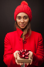 a woman in a red winter hat and coat holding a Christmas gift