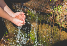 washing hands in a stream