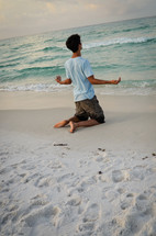 man on his knees in prayer to God at a beach