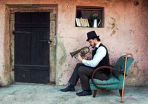 man sitting in a chair playing a trumpet