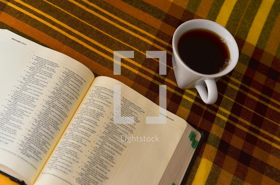 Bible and coffee mug on a plaid table cloth