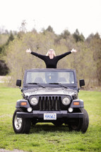 woman with outstretched arms in a Jeep