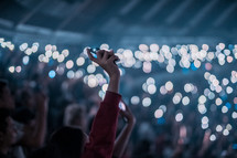 crowds holding up cellphone lights at a concert