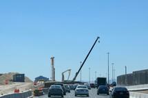 construction cranes over a freeway under construction