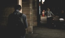 man with a backpack walking on a city sidewalk at night