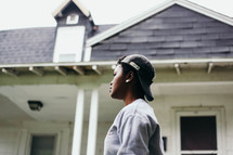 African American youth in a backward ball cap standing in front of a house