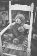 A teddy bear sitting in a rocking chair
