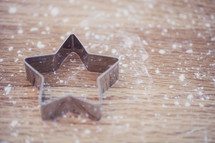 flour on a table and a star cookie cutter