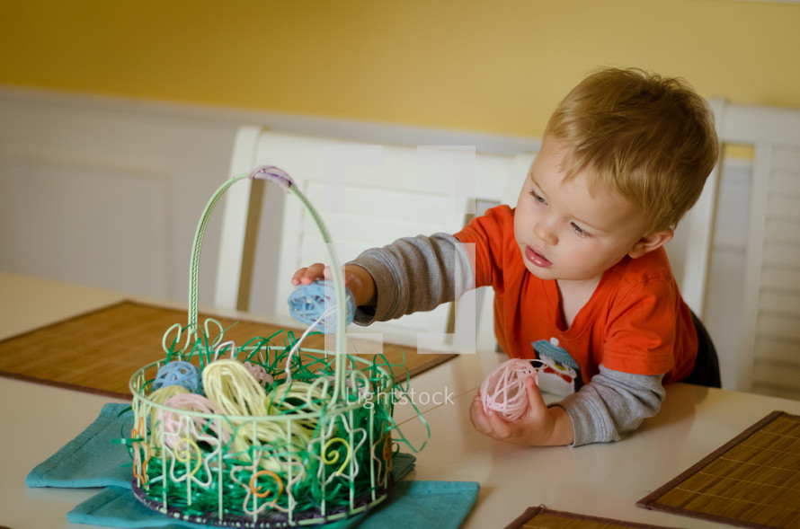 a toddler boy playing with an Easter basket on a table