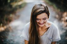 smiling teen girl looking down
