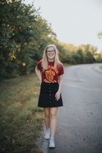 a teen girl walking down a rural road