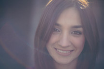 smiling face of a woman with a halo of light around her face