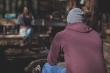 A man in a beanie sitting by the campfire