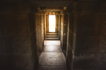 Bright sunlight at the end of a stone hallway.