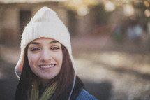 A young woman smiling and wearing a white beanie