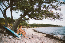 surfer resting by a tree on a beach