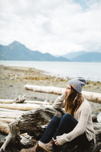 a woman sitting on driftwood on a beach