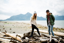 a couple walking around driftwood on a shore