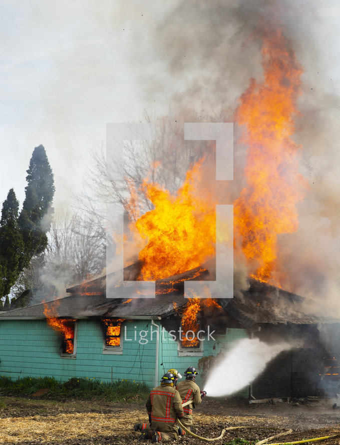 fire fighters putting out a house fire