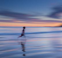 blur of a running boy on a beach