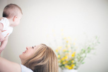 Mother holding daughter in the air with yellow flowers in the background.