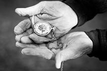 Elderly hands holding a pocket watch.