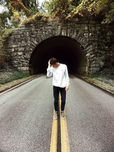 man standing in the middle of a road in front of a tunnel