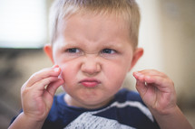 A young boy makes a silly face.