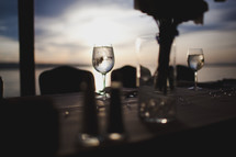 wine glasses and place settings on a table under low light